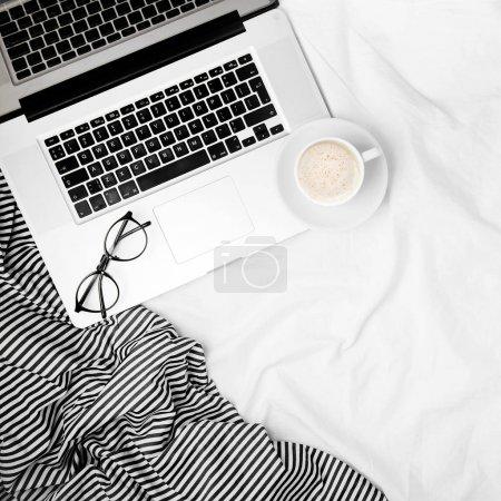 Photo pour Espace de travail avec ordinateur portable et le café dans le lit. Notion de matin. Poser de plat - image libre de droit