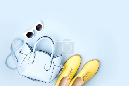 Lovely blue ladies bag, sunglasses and stylish yellow shoes. Spring fashion concept