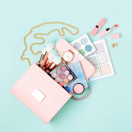 Photo pour Produits cosmétiques découlant de la trousse de maquillage sur fond bleu pastel. Vue plate Lapointe, haut. Concept de mode - image libre de droit