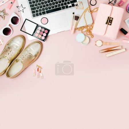Fashion blogger workspace with laptop and female accessories, cosmetics products on pale pink table.