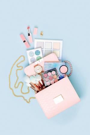 Photo pour Produits cosmétiques découlant de la trousse de maquillage sur fond bleu pastel. - image libre de droit