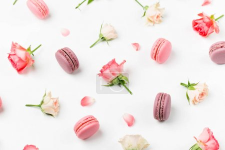 Seamless background with macaroons and roses isolated on white background