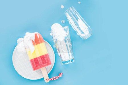 Photo pour Éponge en forme de crème glacée et de verre sur fond de mousse de savon. Concept de lavage de vaisselle. Couche plate, vue du haut. - image libre de droit