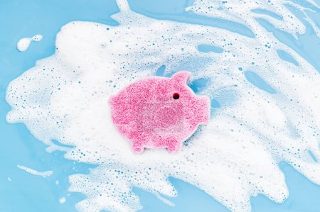 Photo pour Éponge de mignon cochon en forme de fond de mousse de savon. Concept de lavage de vaisselle. Couche plate, vue du haut. - image libre de droit