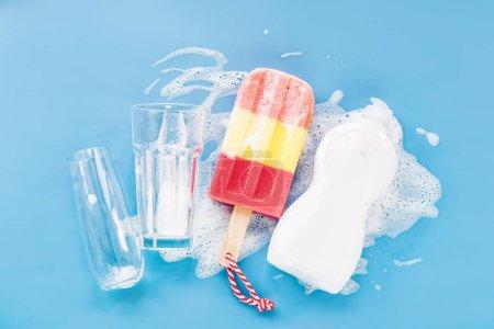 Photo pour Bouteille avec lessive et éponge en forme de glace et verre sur fond de mousse savonneuse. Concept de lavage de vaisselle. Couche plate, vue du haut. - image libre de droit