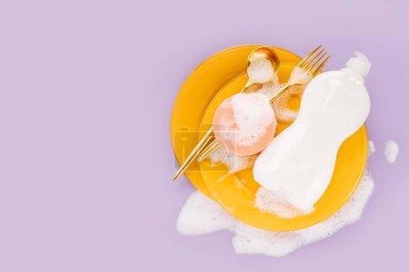 Photo pour Bouteille avec lessive, éponge et plaques jaunes sur fond de mousse savonneuse. Concept de lavage de vaisselle. Couche plate, vue du haut. - image libre de droit