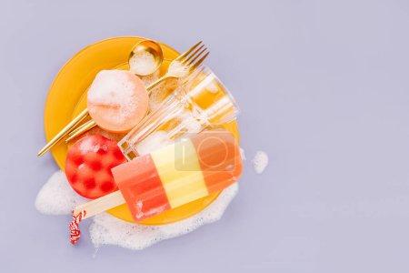 Photo pour Plaques jaunes avec cuillères, fourchettes et éponge sur fond de mousse savonneuse. Concept de lavage de vaisselle. Couche plate, vue du haut. - image libre de droit