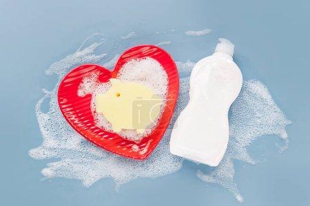 Photo pour Bouteille avec lessive, éponge et plaques sur fond de mousse savonneuse. Concept de lavage de vaisselle. Couche plate, vue du haut. - image libre de droit