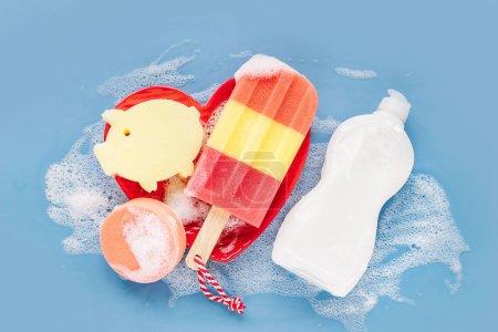 Photo pour Bouteille avec lessive et éponges sur fond de mousse savonneuse. Concept de lavage de vaisselle. Couche plate, vue du haut. - image libre de droit