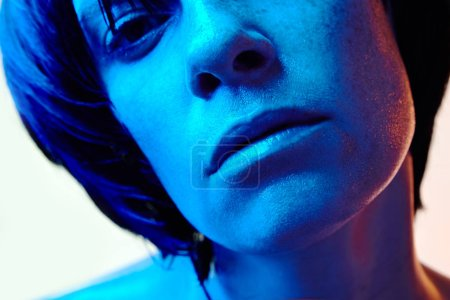 Close-up portrait of beautiful woman with short black hair and blue light