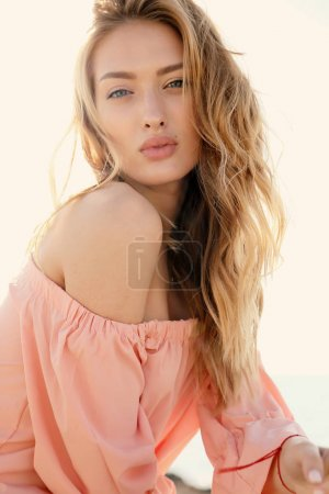 Photo for Fashion outdoor photo of beautiful girl with blond hair in elegant clothes posing at summer sunset beach - Royalty Free Image
