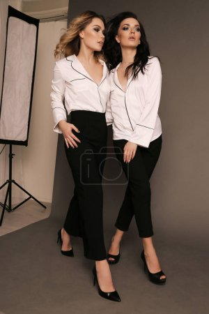 Photo for Fashion photo of two beautiful women with dark hair in elegant clothes posing at studio - Royalty Free Image