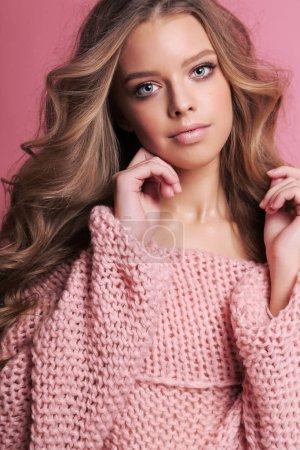 Photo pour Photo de mode de belle jeune fille aux cheveux blonds dans un confortable cardigan rose posant en studio - image libre de droit
