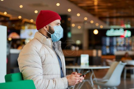 Photo for A caucasian man with a beard wearing a medical face mask to avoid the spread coronavirus (COVID-19). A fellow with a surgical mask on the face holding a smartphone in the shopping center. - Royalty Free Image