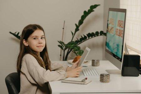 Photo pour Enseignement à distance. Une jeune fille aux cheveux longs qui étudie à distance en ligne. Une fille heureuse apprend une leçon à l'aide d'un ordinateur tout-en-un à la maison. Enseignement à domicile. - image libre de droit