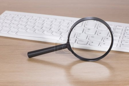 Magnifying glass balanced upright near a keyboard