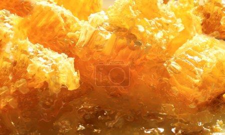 Photo pour Tranches de délicieux nid d'abeille doré, avec le miel collant doux brillant et parfumé qui en résulte - image libre de droit