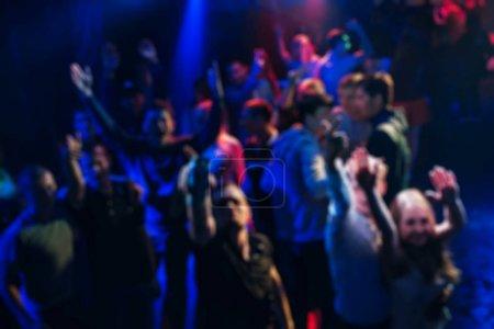 Photo pour Silhouettes floues joyeux compagnons de danse au concert avec vos mains et joyeuse - image libre de droit