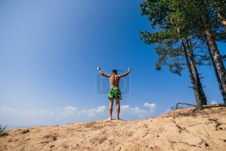 Photo for Man with his hands up on top of a hill on a summer day symbolizes happiness, freedom and success - Royalty Free Image