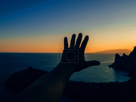 Photo pour Main contre le coucher de soleil dans la nature symbolise la liberté et la protection de la nature - image libre de droit