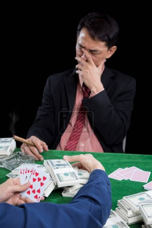 The male gambler uses hand off the face with stressed when conte