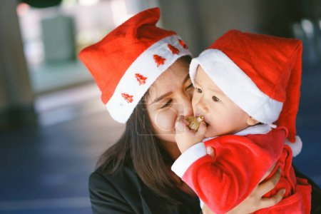 Asian mother holding baby in santa suit
