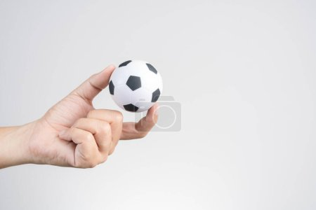 Photo for Hand holding small soccer ball or football on white background - Royalty Free Image