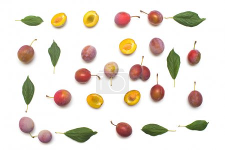 Berry plums with leaves isolated on white background. A useful fruit for health, vitamins. Flat lay, top view