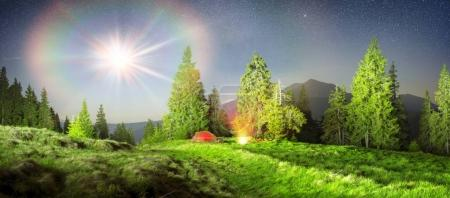 Tent and cyclist at night in Carpathian Mountains