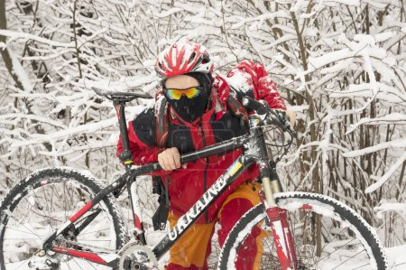 A man walks on bicycle in snowfall