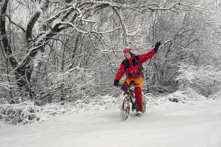 A man walks on bicycle in snowfall