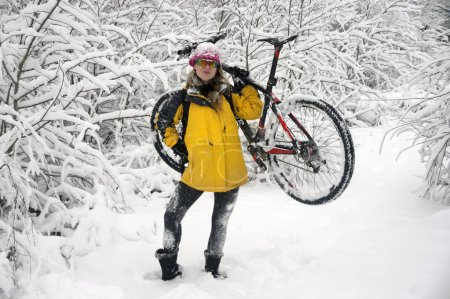A woman walks on bicycle in snowfall