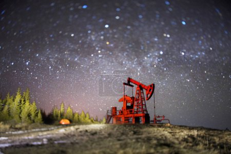 Classical technology of oil and gas extraction by electric pumps against background of eternal beauty of stars, Ukrainian Carpathians