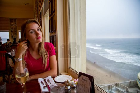 Girl sitting by the window with a ocean view at th...