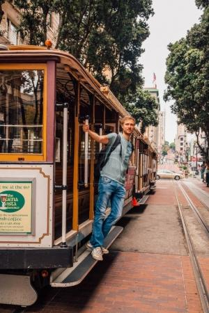 Young man driving on the cable car in San Francisco by the very edge of the cabin. April 10, 2017. USA.
