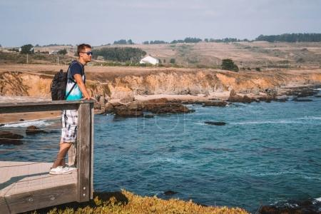 Young man standing on the edge of the pier by the Californian coastline looking into the ocean.