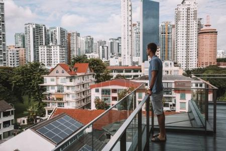 Young man standing on the balcony at the Wangz hotel in Singapore looking down the city landscape. August 30, 2017.