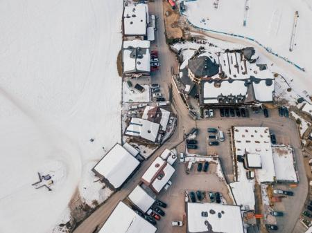 Aerial view of the mountain ski resort village in Austrian Alps with large mountain slopes, skiers, snowboarders, ski lifts and small winter town.