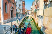 Italy, Venice. April 12, 2018. Beautiful view of traditional Gondolas on famous Canal Grande with Rialto Bridge at sunset, near narrow canals in Venice, Italy with retro vintage Instagram style filter.