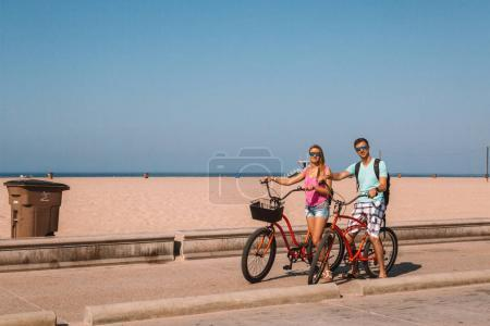 Young couple riding bicycles down the Venice beach in Los Angeles near Santa Monica pier