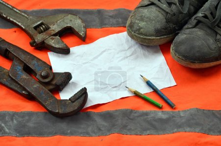 Adjustable wrenches with old boots and a sheet of paper with two