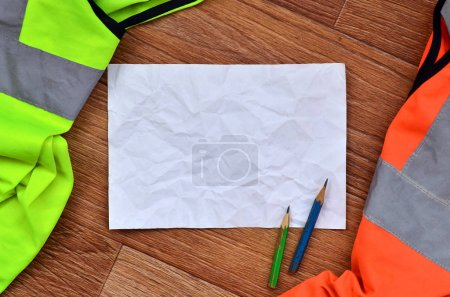 Photo for A crumpled sheet of paper with two pencils surrounded by green and orange working uniforms. Still life associated with repair, railway or plumbing works - Royalty Free Image