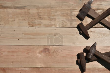 Photo for A few rusty hammers on a wooden background. Obsolete household tools made of rusty metal lie on a wooden table in a workshop. The concept of repair and construction works - Royalty Free Image