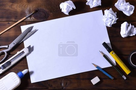 A school or office still life with a white blank sheet of paper and many office supplies. The school supplies lie on a brown wooden background. Place for text