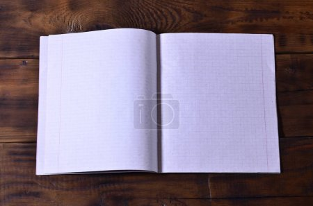 Photo of a clean white school checkbook on a brown wooden background. Idea or message concept. Plenty of space for text