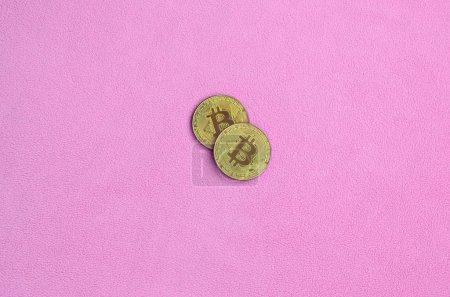 Photo pour Deux bitcoins dorés reposent sur une couverture en tissu polaire rose clair doux et moelleux. Visualisation physique de crypto monnaie virtuelle - image libre de droit