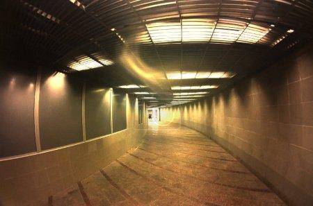 Dark interior of the underground passage with electric lighting