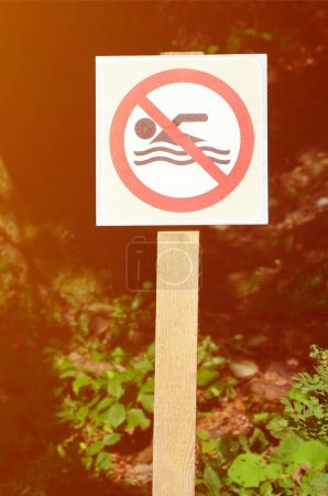 A pillar with a sign denoting a ban on swimming. The sign shows a crossed-out floating person