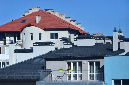 Roofs of modern houses under a cloudless sky. Metal roofing method