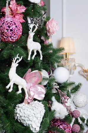 Decorating Christmas tree close up. Decoration bulb, fir tree, pink x-mas toys and lights. Use for Christmas and New years celebration background